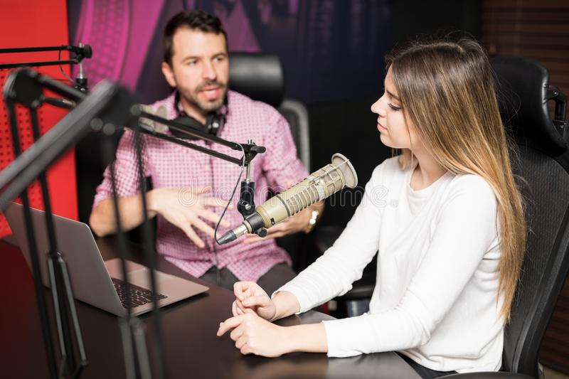 Radio hosts moderating a live show at station. Young hispanic male and female host moderating a live radio show at radio station stock photography
