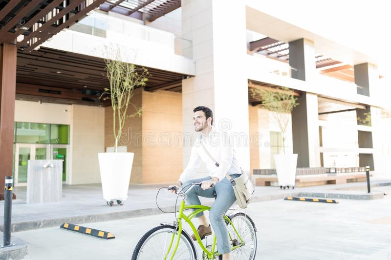 Cost Efficient Way Of Traveling Everyday. Young Hispanic male manager cycling to work in city royalty free stock photo