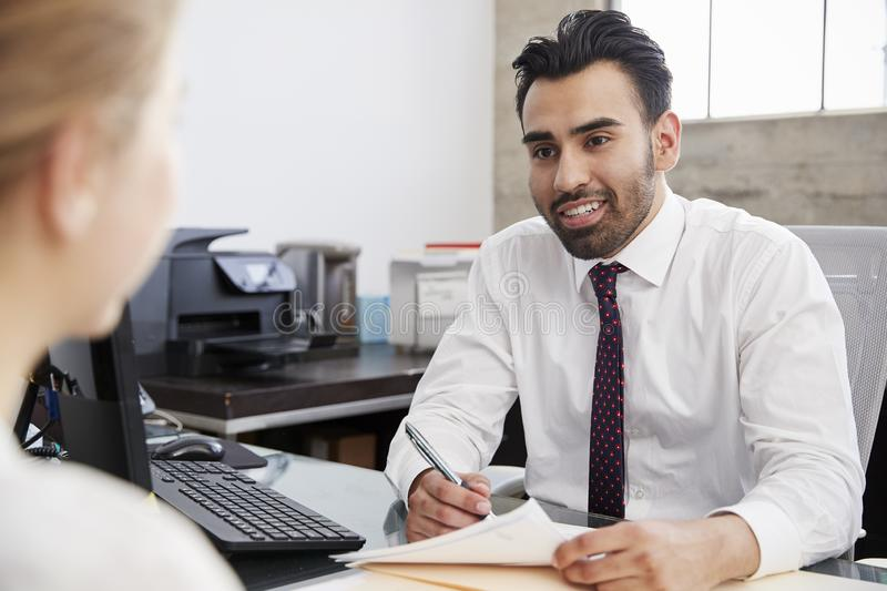 Young Hispanic male professional in meeting with woman in office stock photo