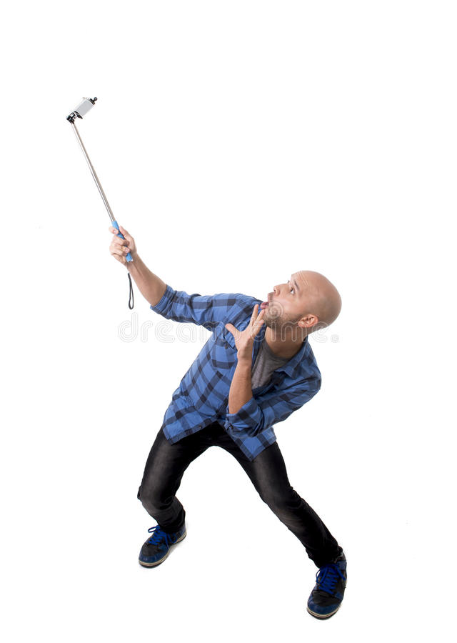 Young Hispanic man in casual shirt having fun shooting mobile phone selfie picture holding stick royalty free stock photo