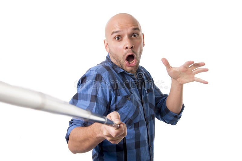 Young Hispanic man in casual shirt having fun shooting mobile phone selfie picture holding stick. Young Hispanic man in casual shirt having fun shooting mobile stock image