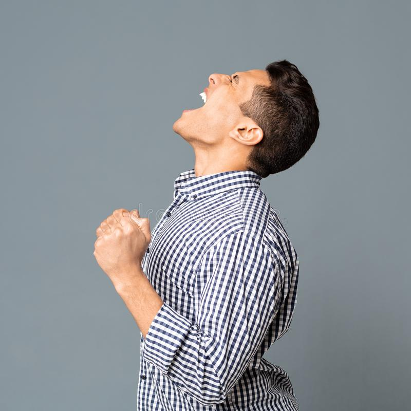 Emotional Latin Guy With Clenched Fists Screaming Furiously, Side View. Young Hispanic Man With Clenched Fists Yelling And Roaring Furiously On Gray Studio stock photos