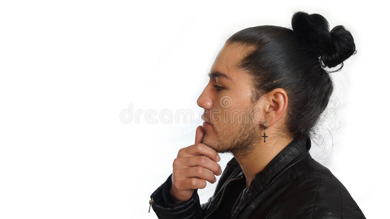 Young hispanic man with gathered hair done bow wearing black t-shirt and black leather jacket, with his hand on jaw stock photography