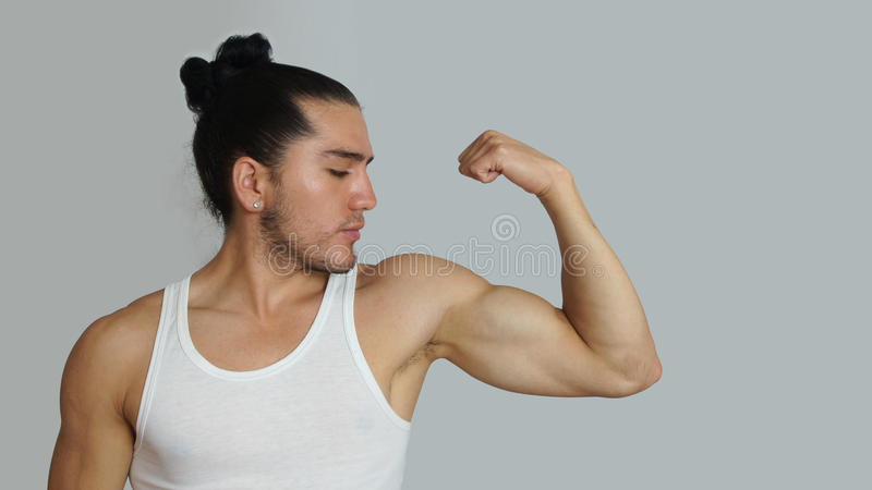Young hispanic man with hair pulled up bun in white sleeveless t-shirt showing muscles of his arm stock photography