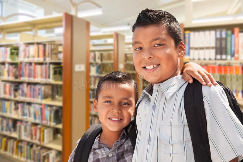 Young Hispanic Student Brothers In Library stock photos