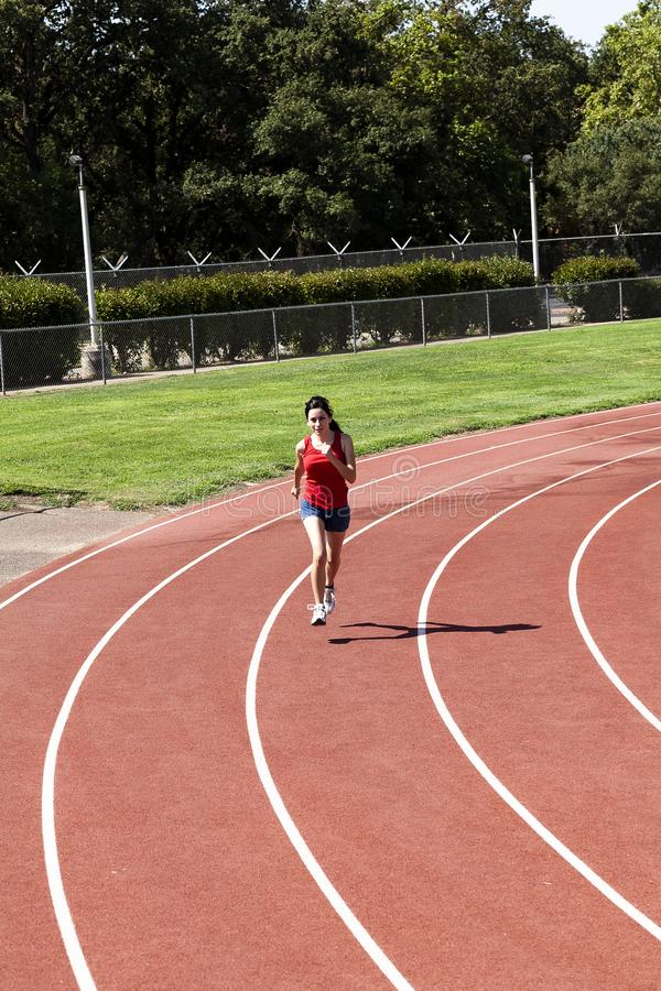 Young Hispanic Woman Running On Track Red Top Blue Shorts stock photo