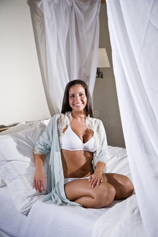 Young Hispanic Woman Sitting On White Canopy Bed Stock Photos
