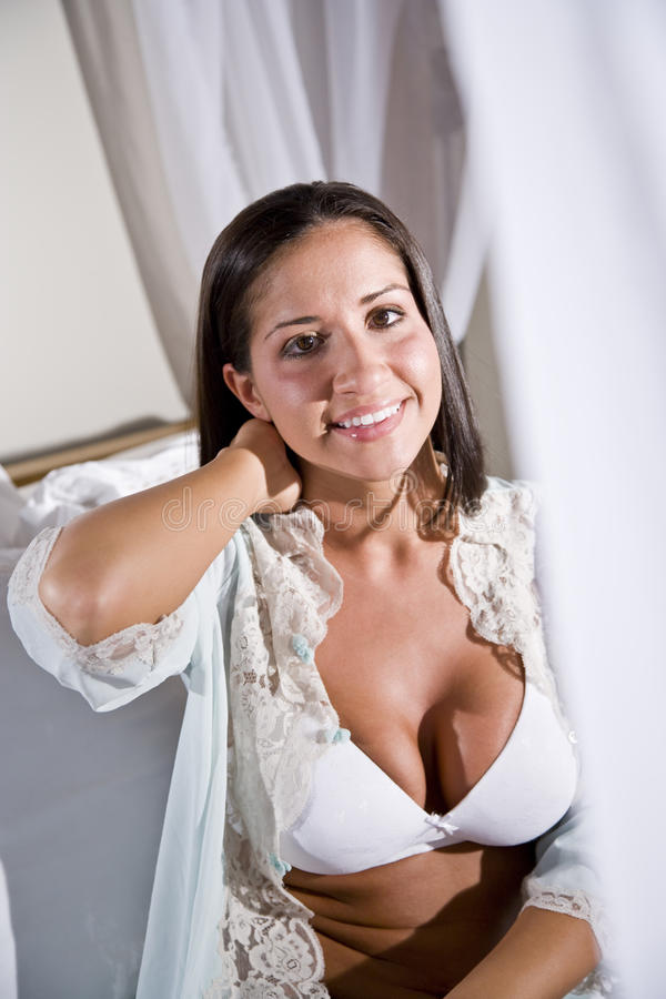 Young Hispanic woman sitting on white canopy bed stock photo