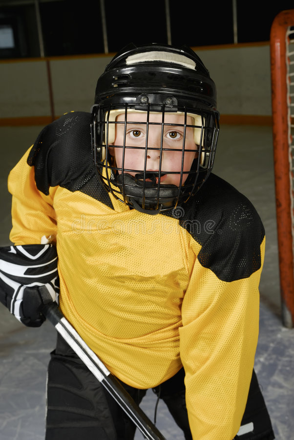 Young Hockey Player. Closeup of a peewee hockey player in his mask stock photo