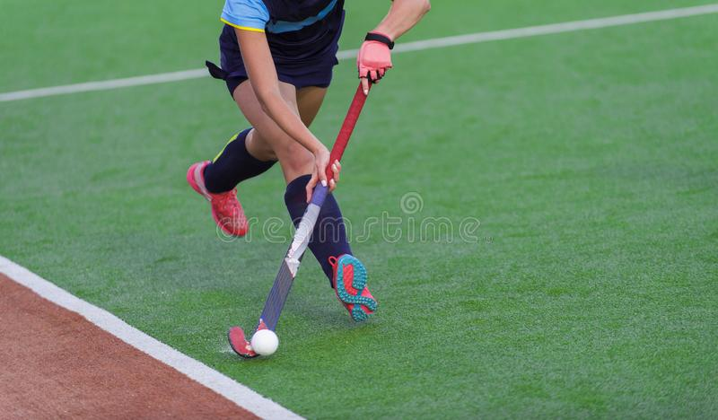Young hockey player woman with ball in attack playing field hockey game.  royalty free stock image