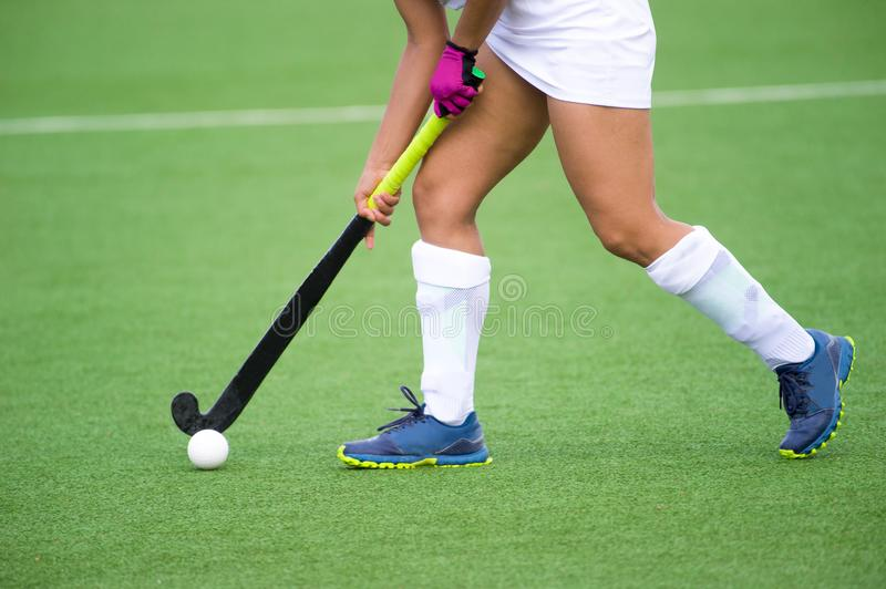 Young hockey player woman with ball in attack playing field hockey game.  stock photo