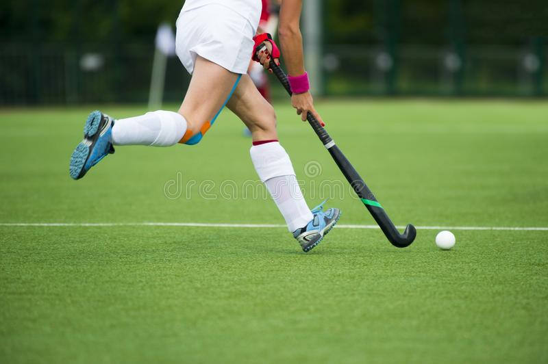 Young hockey player woman with ball in attack playing field hockey game.  stock photos