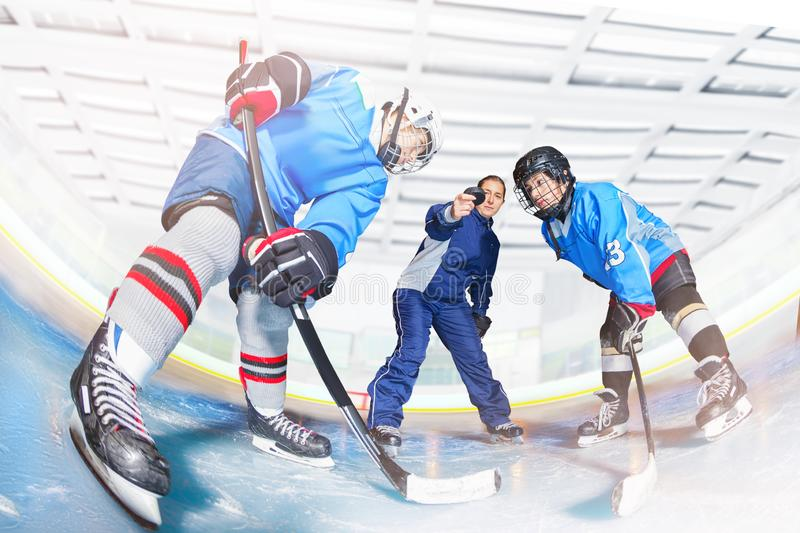 Young hockey players and coach dropping puck. Low-angle portrait of two teenage hockey players and female coach dropping puck royalty free stock images