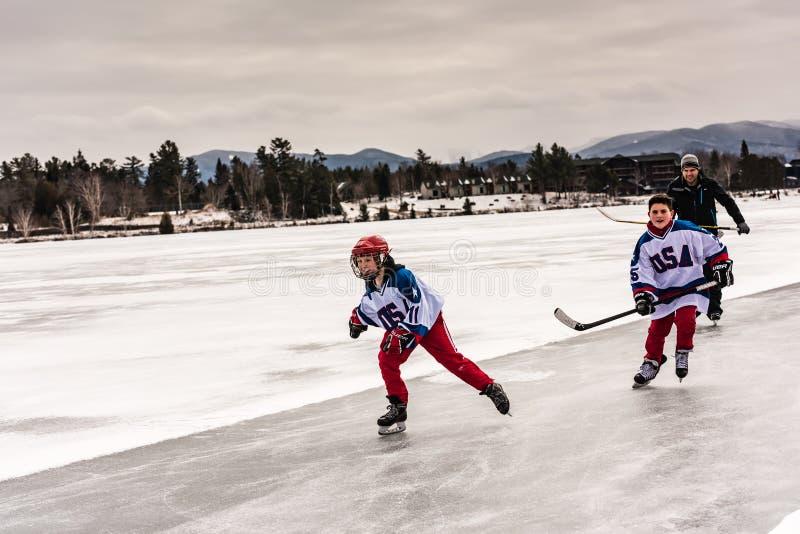 Young Hockey Skiers Skating on Mirror Lake stock photos
