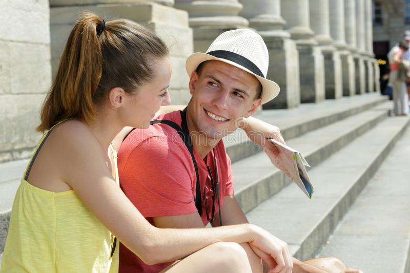 Young holidaymakers sitting on steps building holding map royalty free stock image