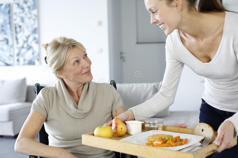 Young homa carer bringing lunch to senior woman stock photos