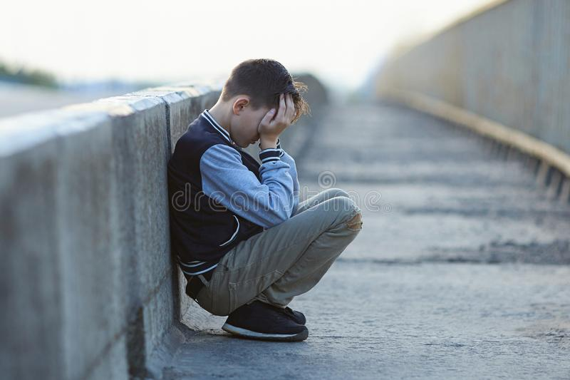 Young homeless boy crying on the bridge stock images