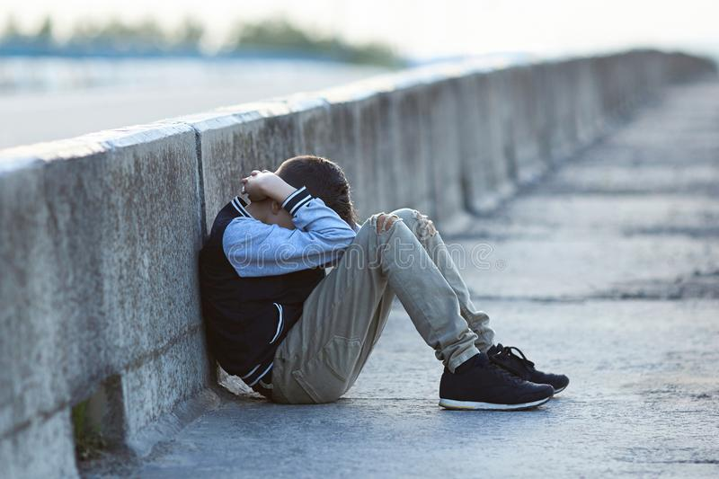 Young homeless boy crying on the bridge. Poverty, city, street, negative emotion stock photography
