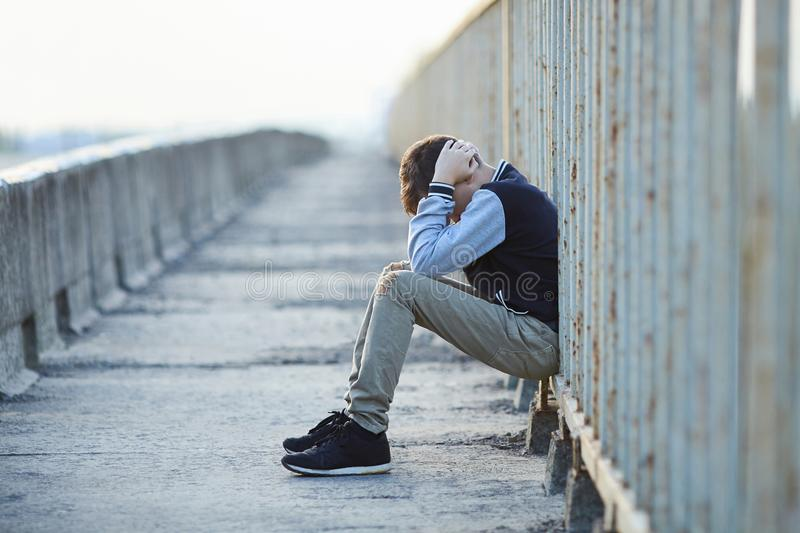 Young homeless boy crying on the bridge. Poverty, city, street, negative emotion royalty free stock images