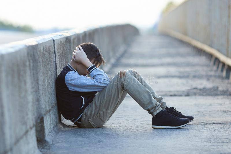 Young homeless boy crying on the bridge. Poverty, city, street, negative emotion royalty free stock photos