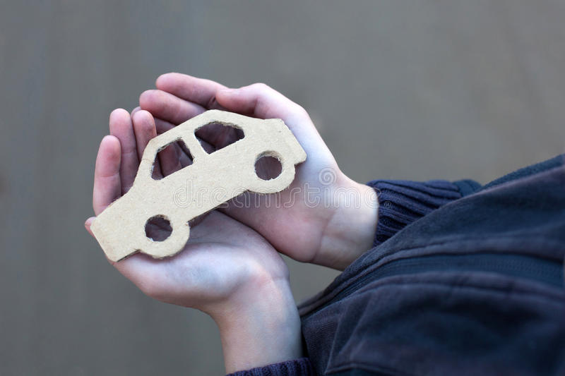 Young homeless boy holds a cardboard car. Dirty hand, dream concept stock images