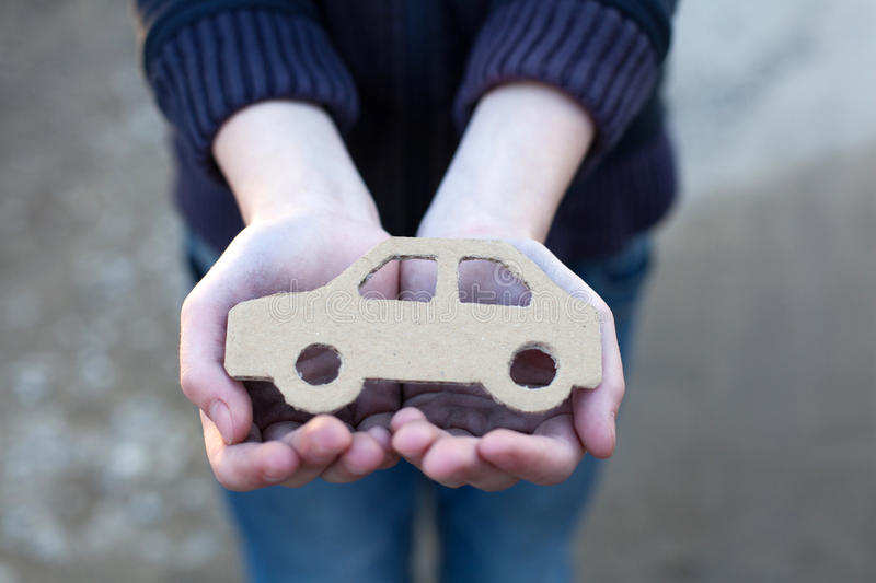 Young homeless boy holds a cardboard car. Dirty hand, dream concept royalty free stock photography