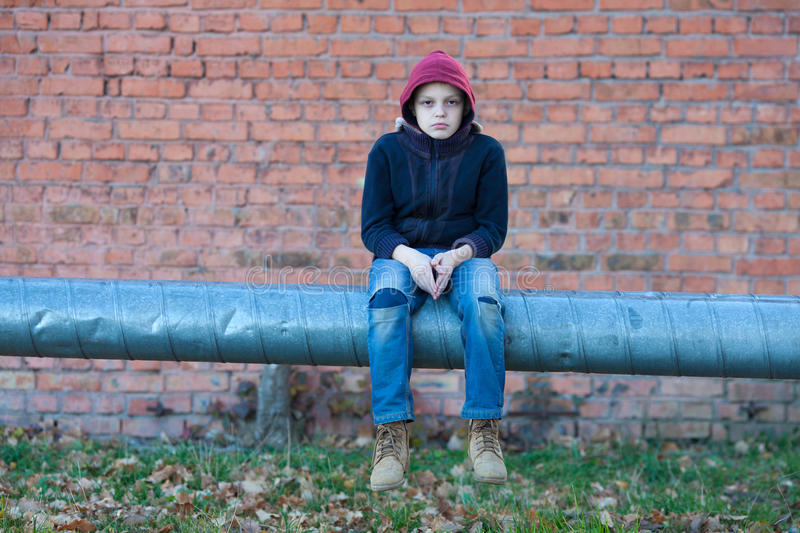 Young homeless boy sits on a pipe with heating. City, street stock images