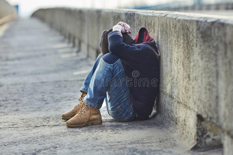 Young homeless boy sleeping on the bridge royalty free stock images
