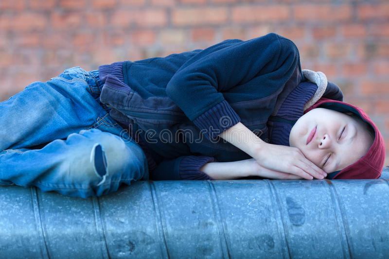 Young homeless boy sleeping on a heating pipe. City, street stock photography
