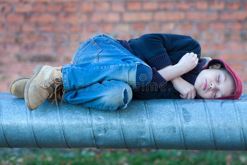Young homeless boy sleeping on a heating pipe. City, street stock image