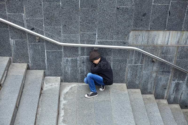 Young homeless boy sleeping on the street. Poverty, city royalty free stock images