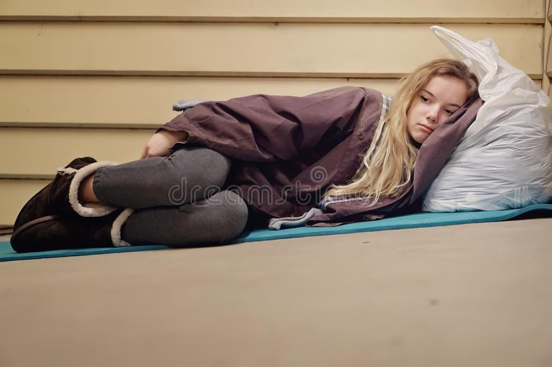 Homeless young teen taking shelter. Young homeless teenage girl finding shelter in the cold winter by an abandoned building royalty free stock image