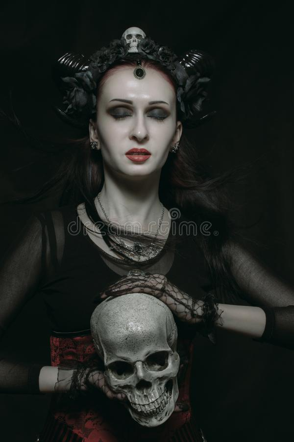Horned lady with skull. Young horned beautiful lady posing over dark background with skull royalty free stock photography