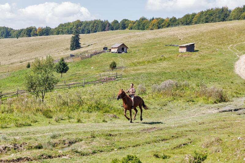Young horseman gallop across the Starishora mountain valley, Ukraine. royalty free stock photos