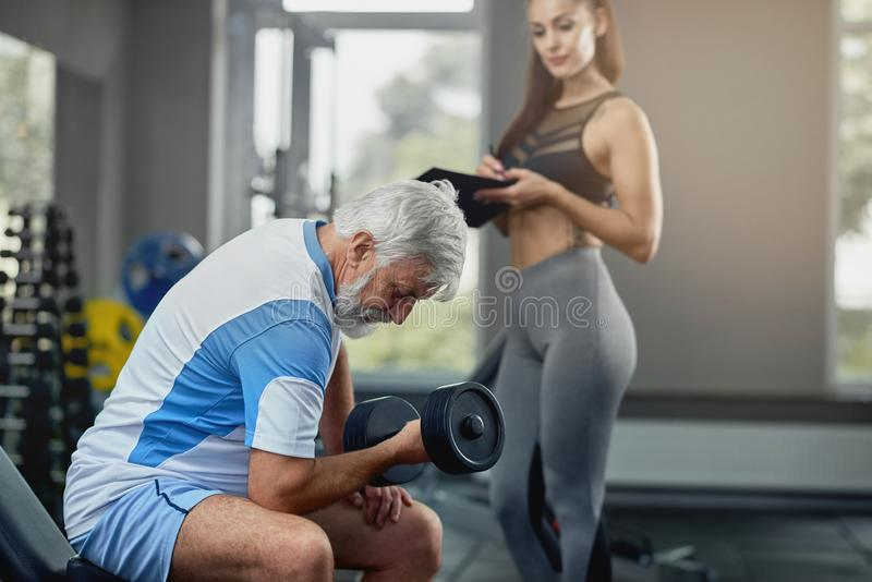 Young hot female personal trainer supporting senior gray man. Young hot female personal trainer supporting senior gray men to properly performing exercises to royalty free stock image