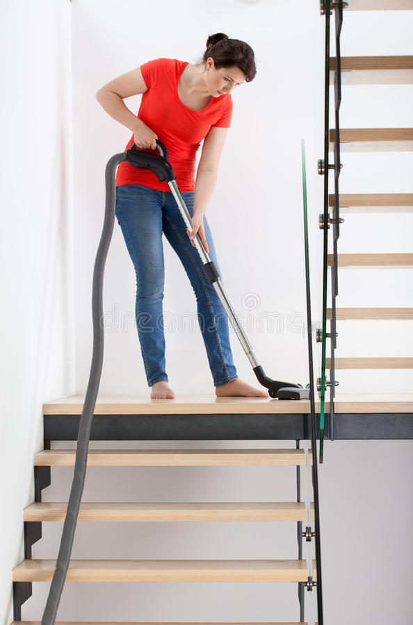 Young housekeeper during hoovering. Vertical view of a young housekeeper during hoovering royalty free stock images
