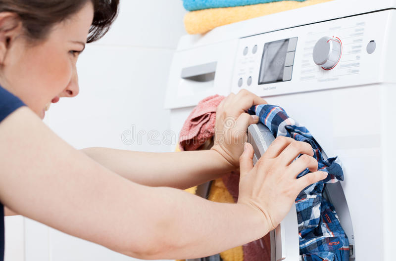 Young housekeeper learning to launder. Horizontal view of young housekeeper learning to launder royalty free stock photography