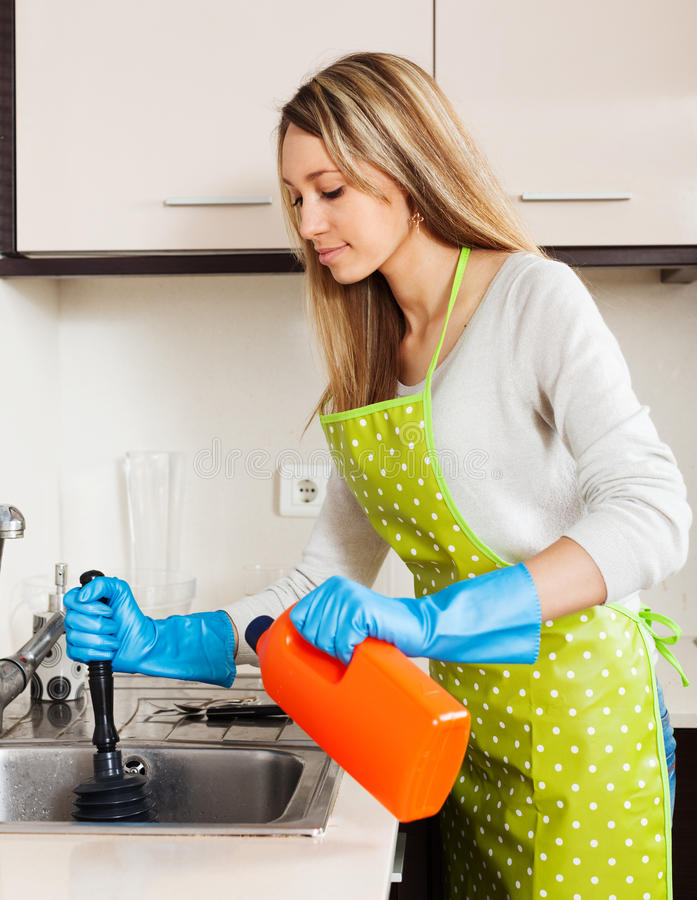 Young housewife cleaning pipe in kitchen royalty free stock photo