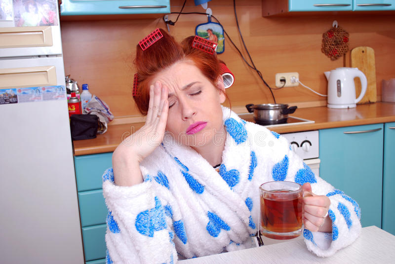 At the young housewife the head has ached. Migraine. The young attractive red girl in a dressing gown wound hair curlers and sits in kitchen has hot tea. At it stock photos