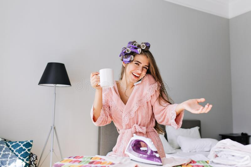 Young housewife in pink bathrobe with curler on head at home at ironing clothes. She speaking on phone, holding a cup. Young housewife in pink bathrobe with stock photography