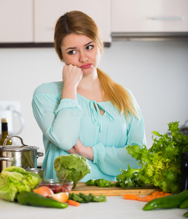 Young housewife tired of cooking vegetables in domestic kitchen. Female tired of vegetarian meal standing at kitchen table royalty free stock photos