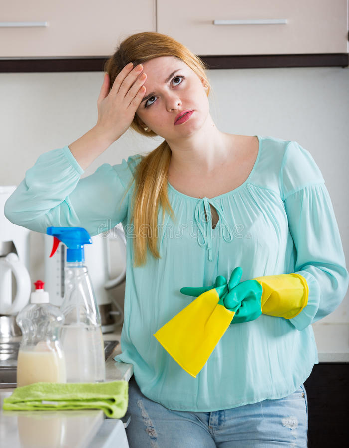 Young housewife tired dusting in domestic kitchen. Portrait of young female maid tired to dust furniture indoors royalty free stock photo