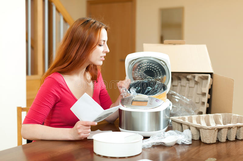 Young housewife unpacking and reading user manual for new crock-pot in her living room. Young woman unpacking and reading user manual for new crock-pot at home stock photography
