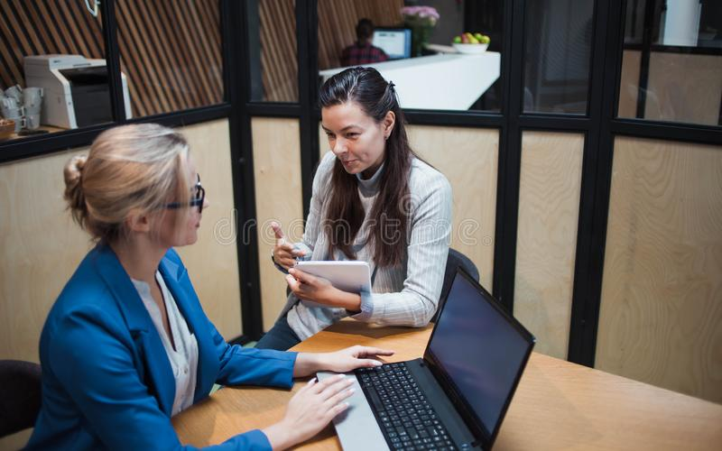Young HR woman interviews a candidate for a job. Business meeting two young women at work discussing the project royalty free stock photos