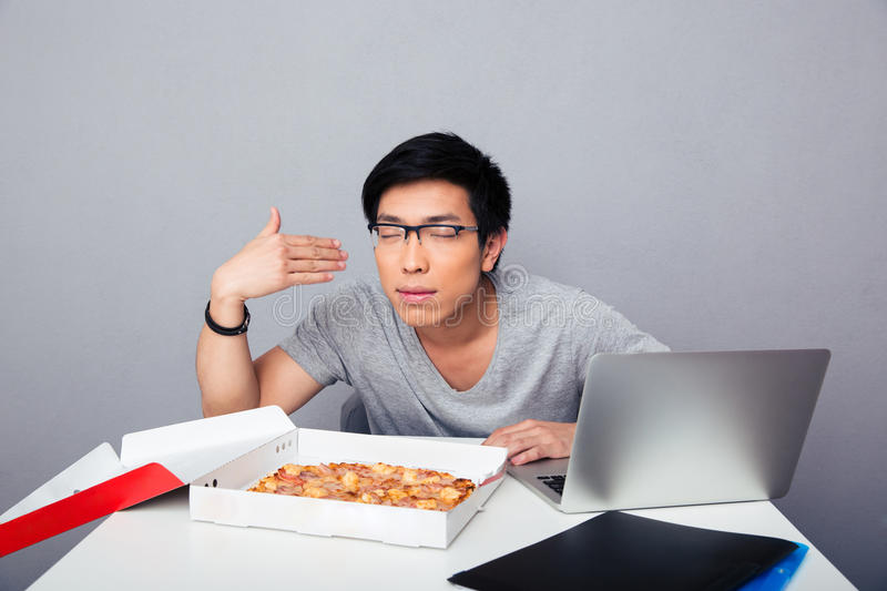 Young hungry man sitting at the table and smelling pizza royalty free stock image