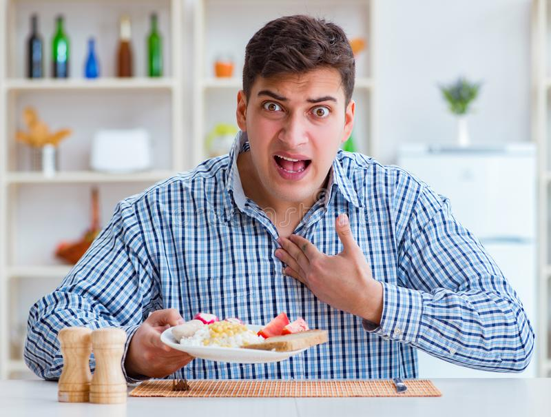 Young husband eating tasteless food at home for lunch. The young husband eating tasteless food at home for lunch royalty free stock image