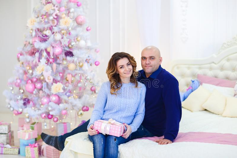 Young husband hugging wife near fir tree and sitting on bed. stock photo