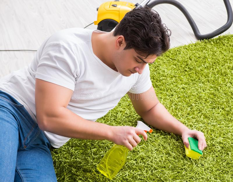 Young husband man cleaning floor at home. The young husband man cleaning floor at home stock photo