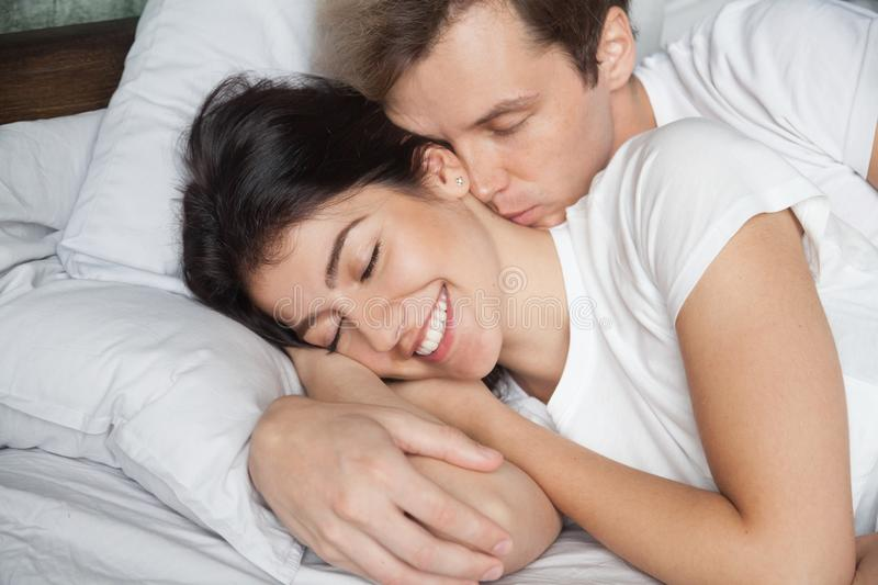 Young husband waking up wife kissing and hugging her royalty free stock photo