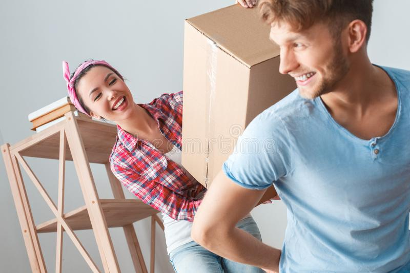 Young couple moving to new place girl helping guy to carry box looking at each other happy close-up royalty free stock photo